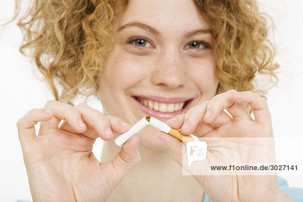 Junge Frau zerbricht die Zigarette  lächelnd  Porträt  Nahaufnahme