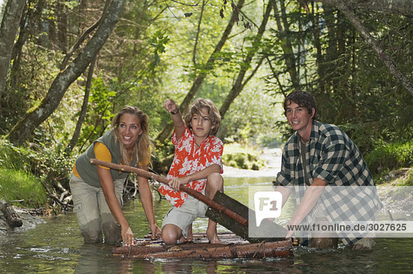 Austria  Salzburger Land  Boy kneeling on timber raft  Parents wading in creek