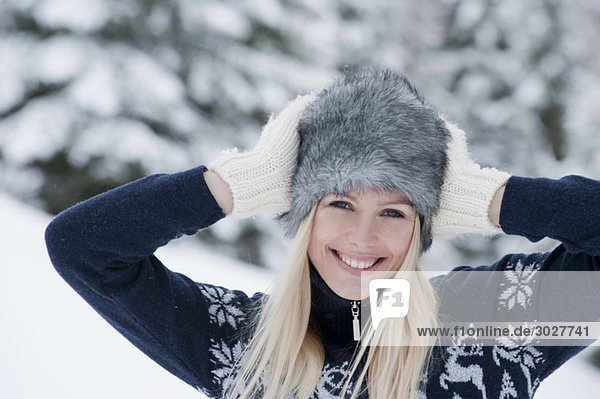 Austria  Salzburger Land  Altenmarkt  Zauchensee  Young woman hands on head  smiling  portrait  close-up
