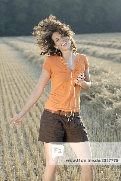 Junge Frau im Feld  tanzen  MP3-Player hören