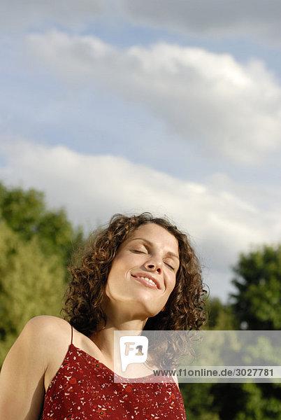 Junge Frau beim Sonnenbaden  Augen zu  lächelnd  Portrait