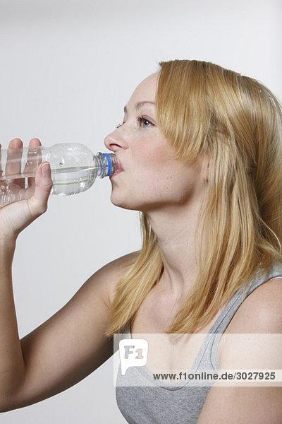 Junge Frau trinkt aus der Wasserflasche  Portrait