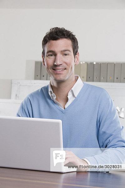 Geschäftsmann im Büro mit Laptop  lächelnd  Portrait
