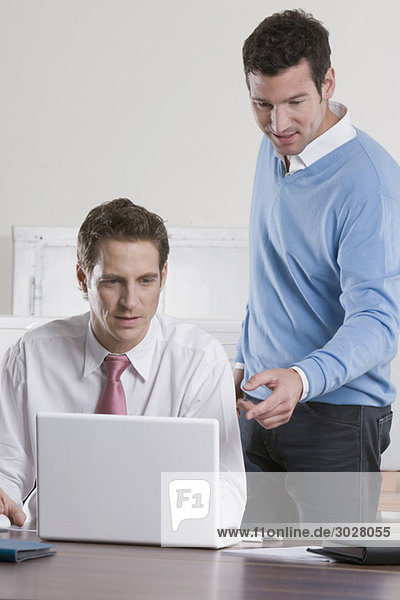 Germany  Munich  two businessmen in office using laptop  smiling  portrait