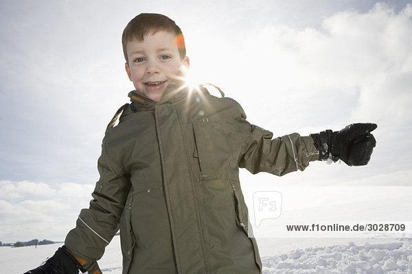 Boy (8-9) in snowy landscape  smiling  portrait