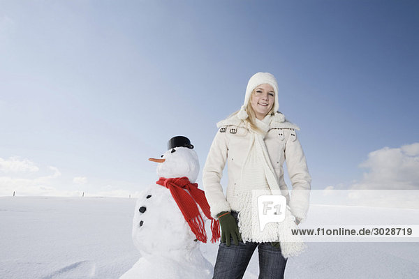 Woman standing next to snowman  portrait