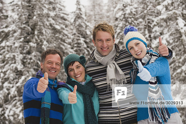Italy  South Tyrol  Young people in winter clothes  thumbs up  portrait