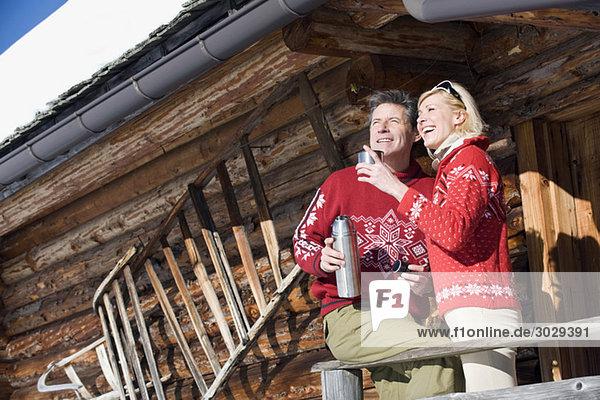 Italien  Südtirol  Seiseralm  Paar auf dem Deck der Blockhütte stehend  Thermoskanne haltend