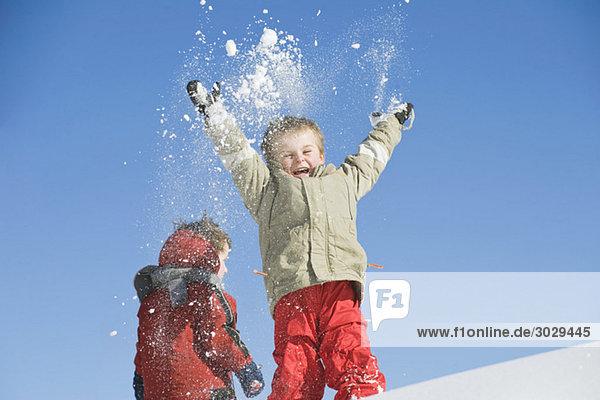 Italien  Südtirol  Seiseralm  Kinder werfen Schnee in die Luft