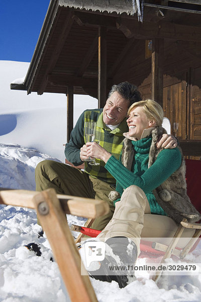 Italien  Südtirol  Seiseralm  Paar vor der Blockhütte sitzend  Sektgläser haltend  lächelnd  Portrait