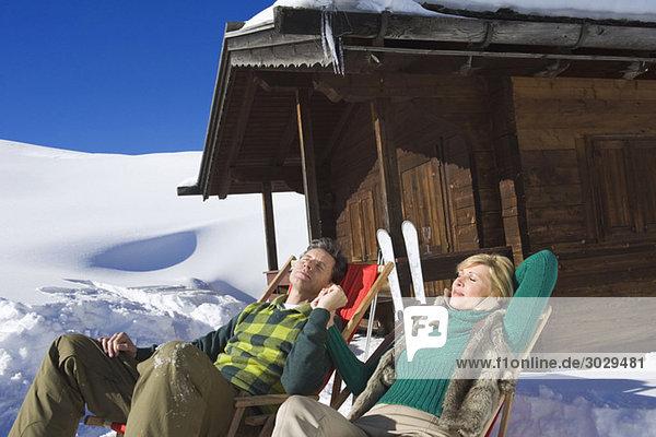 Italien  Südtirol  Seiseralm  Pärchen in Stühlen mit Blockhaus