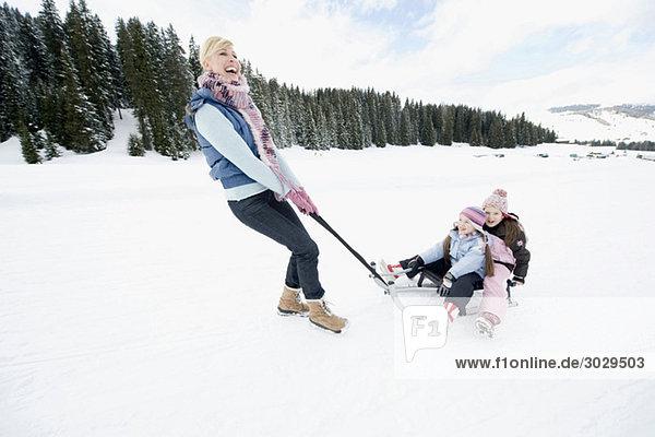 Italien  Südtirol  Seiseralm  Frau mit Kindern (6-7) (8-9) auf dem Schlitten