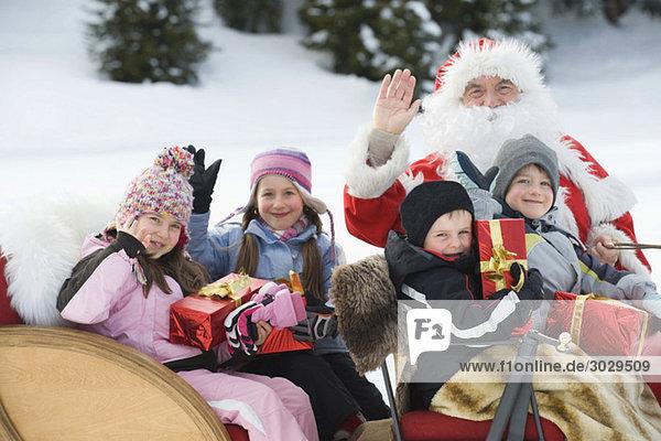 Italien  Südtirol  Seiseralm  Weihnachtsmann und Kinder beim Schlittenfahren