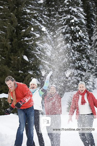 Italien  Südtirol  Seiseralm  Vier Personen werfen Schnee in die Luft