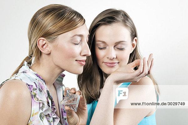 Junge Frauen testen Parfüm  Augen geschlossen  Portrait