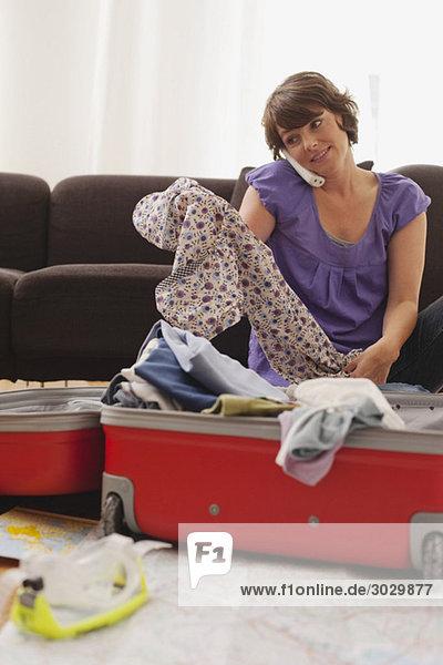 Frau packt Koffer und benutzt Telefon  Portrait