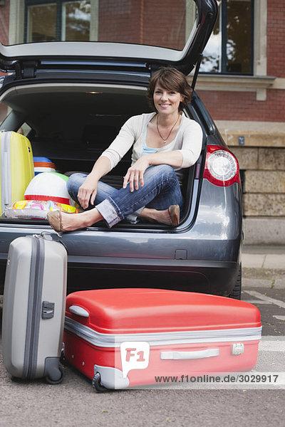 Frau sitzt hinten im Auto  Koffer im Vordergrund