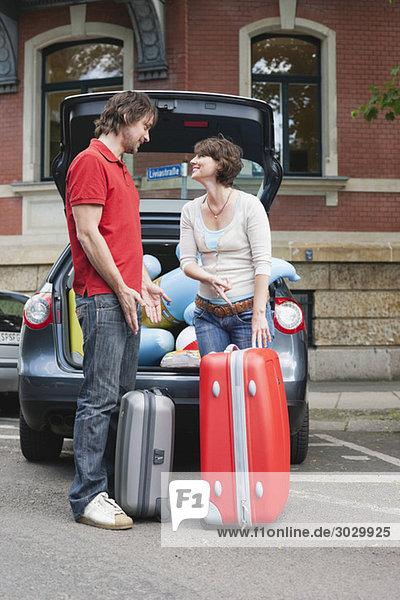 Deutschland  Leipzig  Paar stehend mit Gepäck vor dem Auto