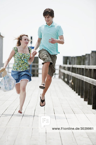 Germany  Bavaria  Ammersee  Young couple running on pier