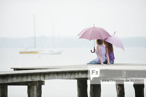 Zwei Frauen sitzen auf dem Steg  halten Regenschirm  Rückansicht