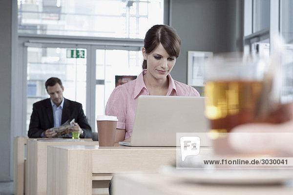 Junge Frau im Cafe mit Laptop  Mann im Hintergrund