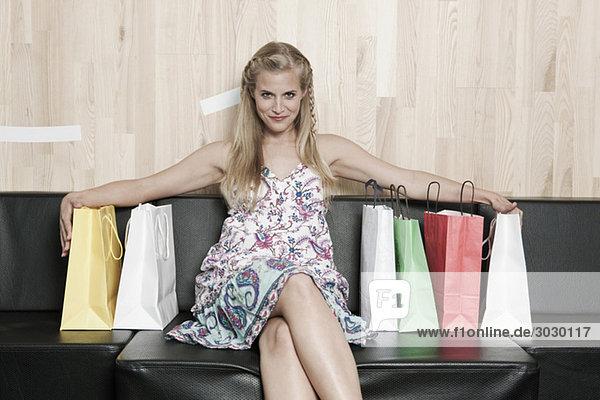 Junge Frau auf Bank mit Einkaufstaschen