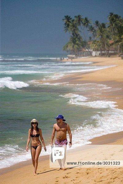 Couple walking along Hikkaduwa Beach  Sri Lanka