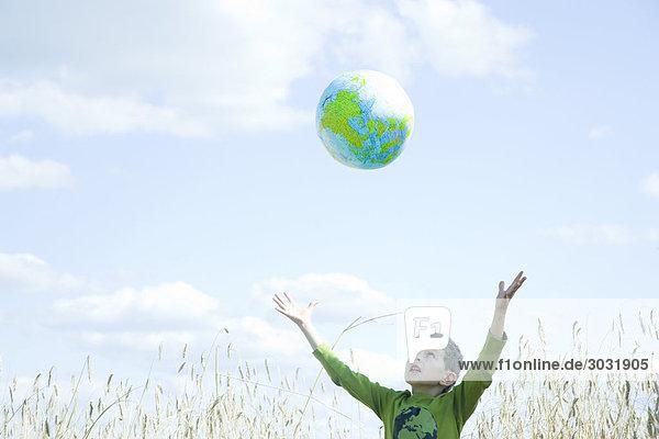 Junge spielt mit Globe in field