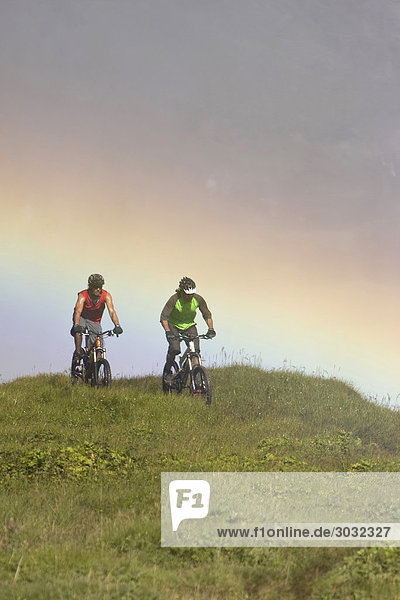 Iceland  Two Men mountain biking in hilly landscape