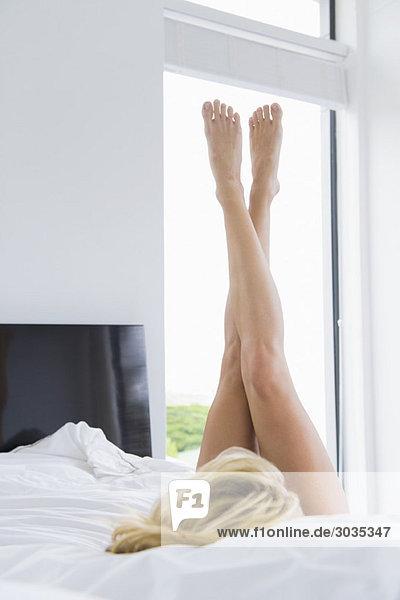 Frau auf dem Bett liegend mit nach oben gestreckten Beinen