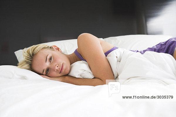 Porträt einer auf dem Bett liegenden Frau