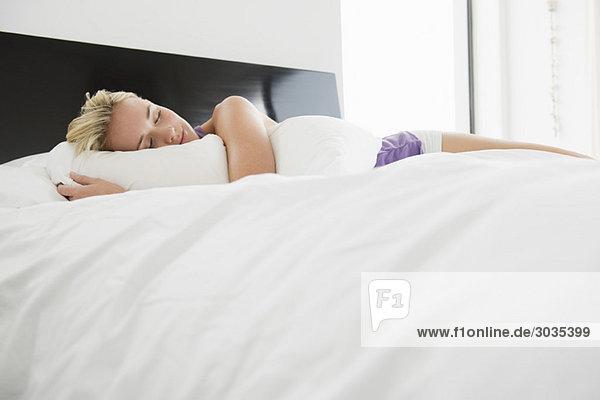 Frau schläft auf dem Bett