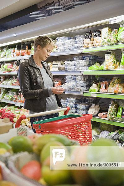Frau kauft verpackte Lebensmittel im Supermarkt ein