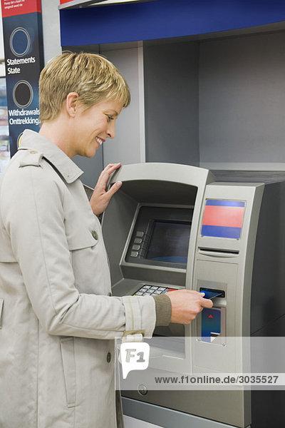 Frau  die eine Kreditkarte in Geldautomat einführt