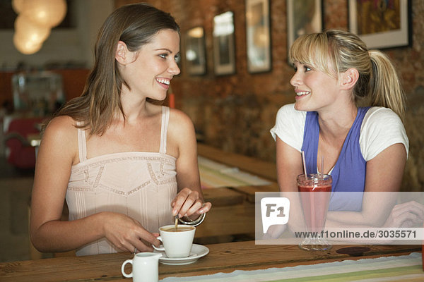 Two women having beverages in a cafe