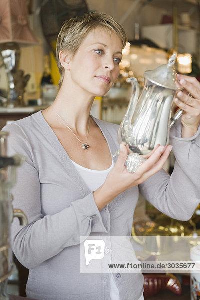 Frau mit Wasserkocher im Laden Frau mit Wasserkocher im Laden