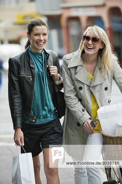 Zwei Frauen  die mit Einkaufstaschen gehen