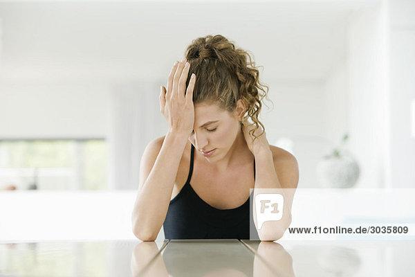 Frau am Tisch sitzend mit dem Kopf in der Hand
