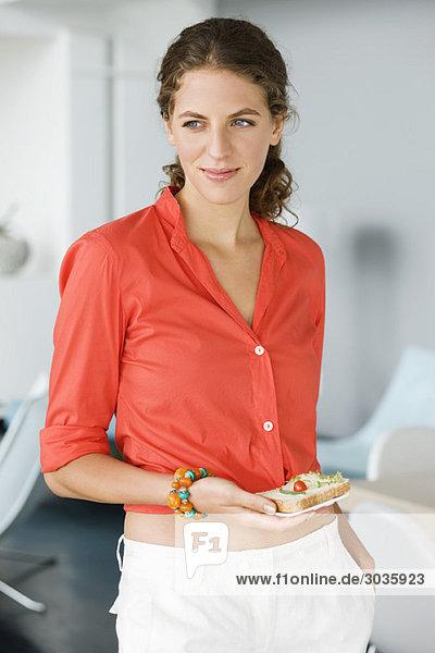 Frau mit einem Sandwich zu Hause