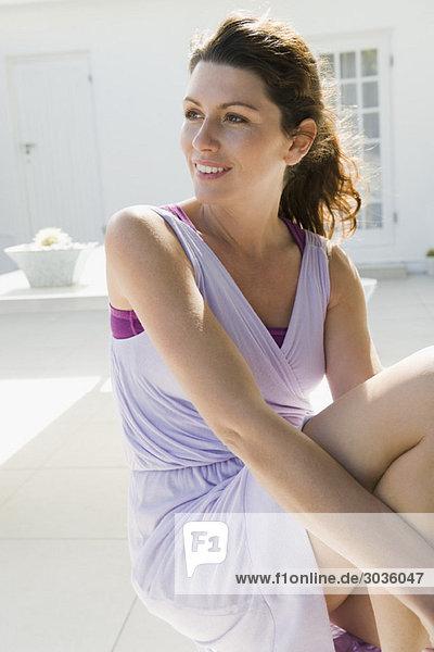 Frau auf dem Boden sitzend und lächelnd