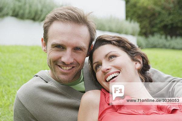 Ein Paar ruht auf dem Rasen und lächelt.