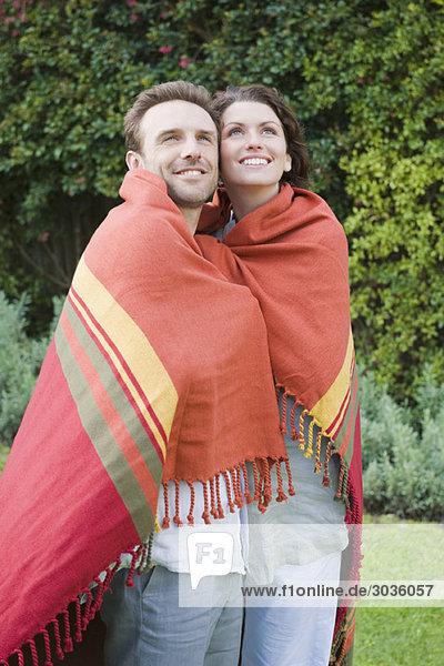 Paar in einen Schal gehüllt und lächelnd