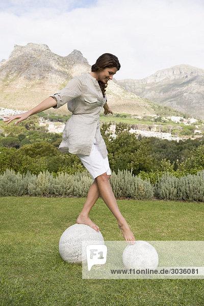 Frau läuft auf runden Steinen