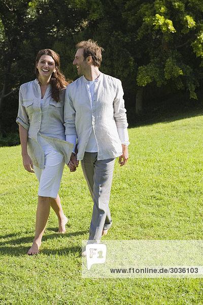 Paar auf Gras gehen und lächeln