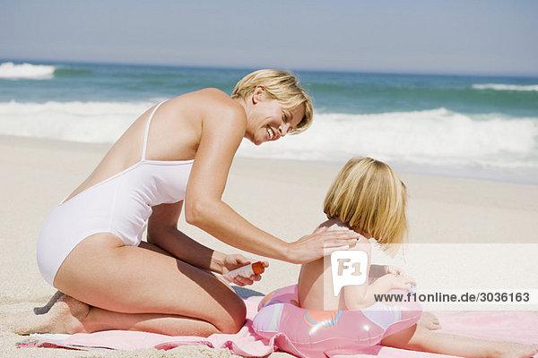 Frau  die Sonnencreme auf ihre Tochter am Strand aufträgt.