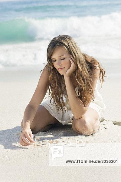 Frau spielt mit Muscheln am Strand