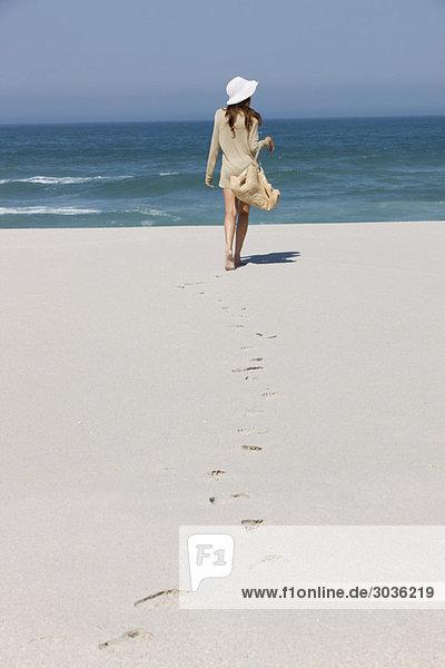 Rückansicht einer am Strand spazierenden Frau
