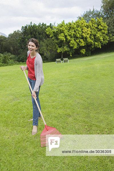 Frau beim Rasen harken und lächeln