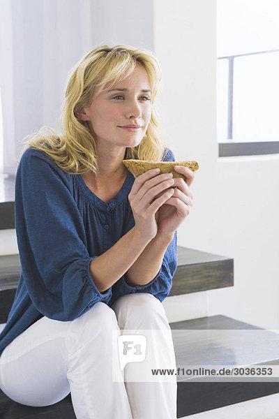 Frau sitzt auf einer Treppe und hält ein Sandwich.