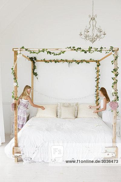 Zwei Mädchen  die ein Bett dekorieren